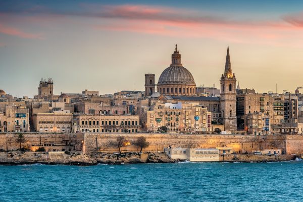 Valletta, Malta: skyline from Marsans Harbour at sunset. The cathedral